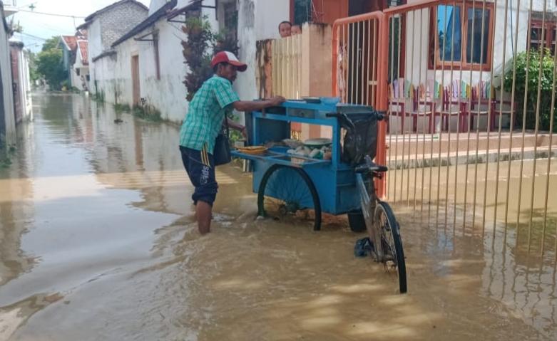 Demi Menafkahi Keluarga, Seorang Pedagang Sate Keliling Tetap Berjualan di Tengah Banjir